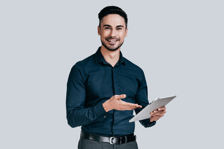 Always ready to help. Handsome young man in shirt pointing on his digital tablet and smiling while standing against grey background