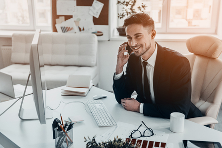 Good business talk. Handsome young man in formalwear talking on the phone and smiling while sitting at the office desk Stock Photo - 72402050