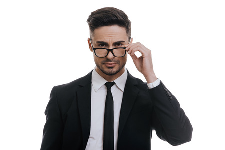 males only: Confident manager. Handsome young man in full suit adjusting his eyeglasses and looking at camera while standing against white background Stock Photo