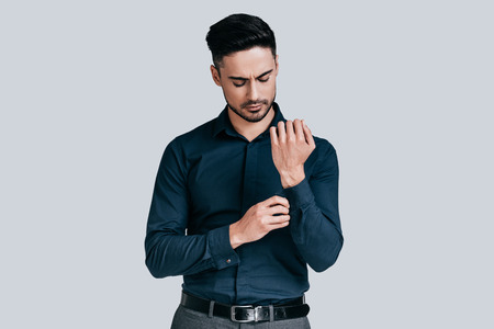 young businessman: Always perfect. Handsome young man adjusting his sleeve while standing against grey background