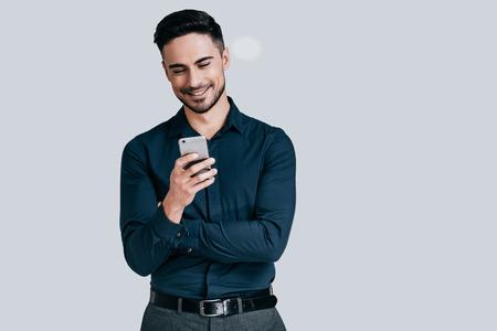 친구로부터 좋은 소식. 똑똑한 전화를 들고 회색 배경에 서있는 동안 미소로보고 잘 생긴 젊은 남자