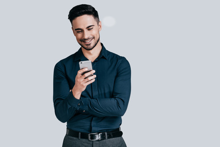 Goed nieuws van vriend. Knappe jonge mens die slimme telefoon houdt en het met glimlach bekijkt terwijl status tegen grijze achtergrond