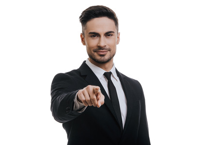 I choose you! Handsome young man in full suit looking at camera and pointing you while standing against white background