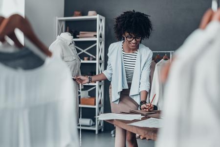 mannequin africain: Chaque détail doit être parfait. Belle jeune femme africaine mesurer la taille avec un ruban et d'écrire les résultats tout en se tenant dans son atelier
