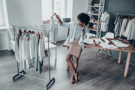 I have exactly what you are looking for! Full length of attractive young African woman talking on smart phone and holding a clothes rack while leaning on the desk in workshop