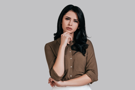 what if: What if... Thoughtful young woman in smart casual wear holding hand on chin and looking away while standing against grey background