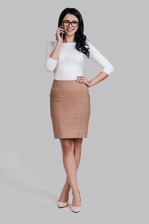 Good business talk.  Full length studio shot of attractive young woman in smart casual wear talking on the phone and looking at camera while standing against grey background