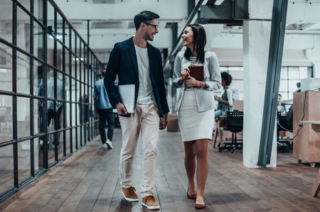 casual office: Mutual understanding. Full length of two young colleagues in smart casual wear discussing business and smiling while walking through the large modern office