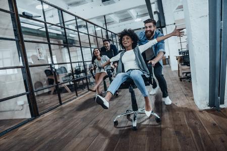 Nós somos os vencedores! Quatro jovens empresários alegres em roupas casual inteligentes se divertem correndo em cadeiras de escritório e sorrindo