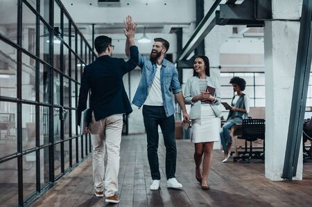 High-five!  Full length of two cheerful young business people giving high-five while their colleague looking at them and smiling Foto de archivo