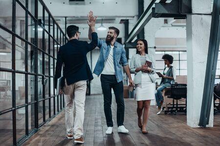 Hoog-vijf! Volledige lengte van twee vrolijke jonge mensen uit het bedrijfsleven geven van high-five, terwijl hun collega kijken naar hen en lacht Stockfoto - 73530135