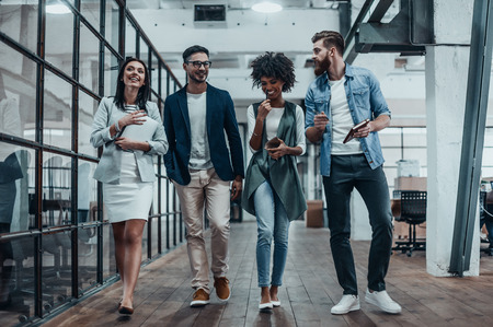 Sharing business experience. Full length of young modern people in smart casual wear having a discussion while walking through the large modern office