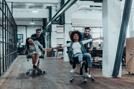 재미로. 사무실 의자에 경주하는 동안 재미 스마트 캐주얼 착용에 젊은 쾌활한 사업 사람들의 그룹
