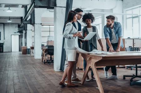 Werken via een aantal concepten. Groep jonge mensen uit het bedrijfsleven samen te werken in creatieve kantoor tijdens het staan ??in de buurt van de houten bureau Stockfoto - 73453132