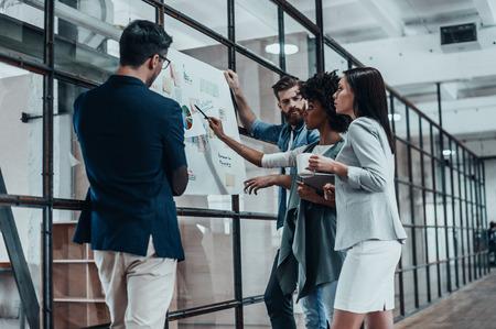 Buscando la decisión correcta. Grupo de gente confía en la planificación de la estrategia empresarial, mientras que la mujer joven apuntando a papel grande se muestra en la pared de vidrio en el pasillo de la oficina