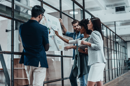 group strategy: Searching for right decision. Group of confident people planning business strategy while young woman pointing at large paper displayed on the glass wall in the office hallway Stock Photo
