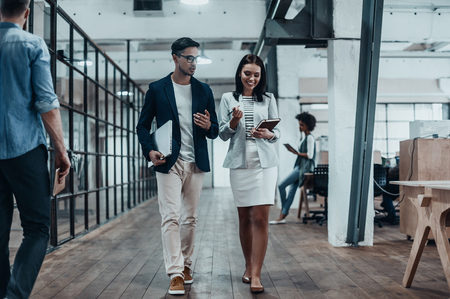 casual office: Giving business advice. Full length of two young colleagues in smart casual wear discussing business while walking through the office corridor Stock Photo