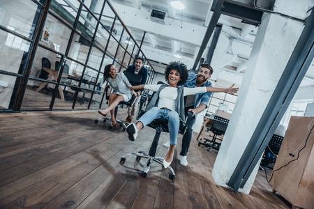 Lavora sodo gioca duro! Quattro giovani allegri uomini d'affari in abbigliamento casual intelligente divertirsi mentre corse sulle sedie di ufficio e sorridente Archivio Fotografico - 73509508