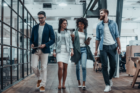 Looking forward to their next meeting. Full length of young modern people in smart casual wear discussing business while walking through the office corridor