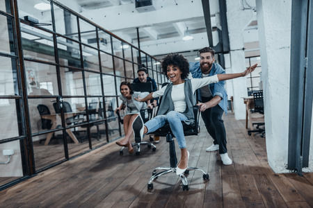 Office fun. Four young cheerful business people in smart casual wear having fun while racing on office chairs and smiling Stockfoto