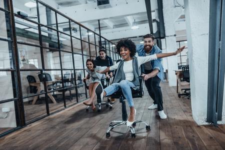 Kantoor leuk. Vier jonge vrolijke mensen uit het bedrijfsleven in smart casual wear plezier hebben tijdens het racen op bureaustoelen en glimlachend