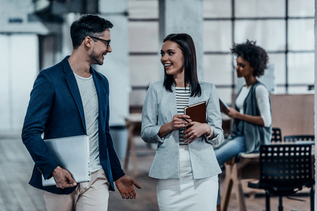 business casual: Sharing fresh office news. Two young colleagues in smart casual wear discussing business and smiling while walking through the office