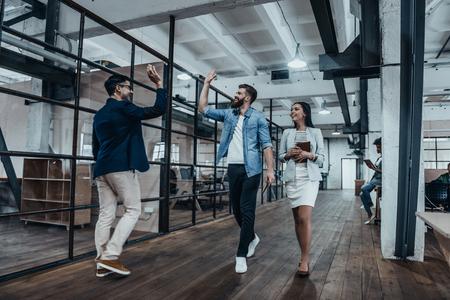 Tape la! pleine longueur de deux joyeux jeunes gens d'affaires donnant haute-cinq tandis que leur collègue en les regardant et souriant Banque d'images