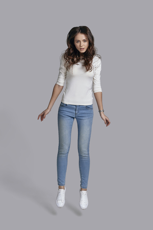 midair: Beauty in mid-air. Full length of attractive young woman in casual wear looking at camera while being in the mid-air against grey background Stock Photo