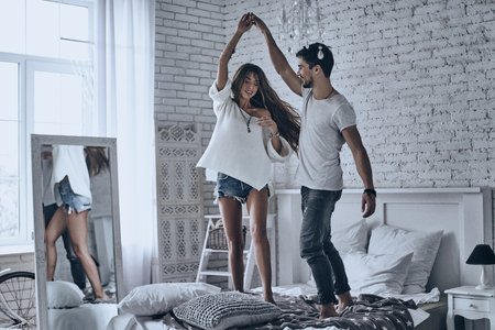 Dansen op het bed. Full length of beautiful young couple holding hands and smiling while dancing on the bed at home Stockfoto