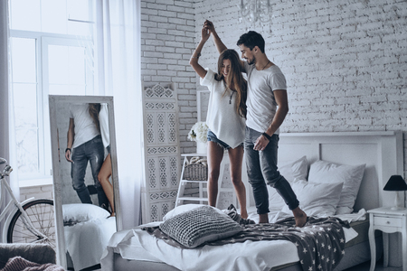 Expressing their love in dance. Full length of beautiful young couple holding hands and smiling while dancing on the bed at home