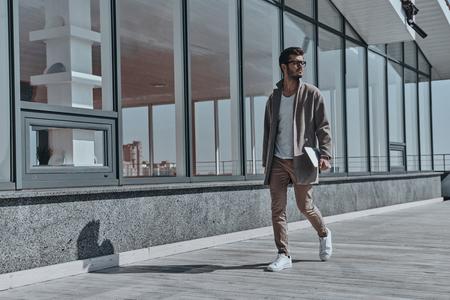 Op weg naar succes. Volledige lengte van de zekere jonge en knappe mens die digitale tablet dragen terwijl in openlucht lopend Stockfoto