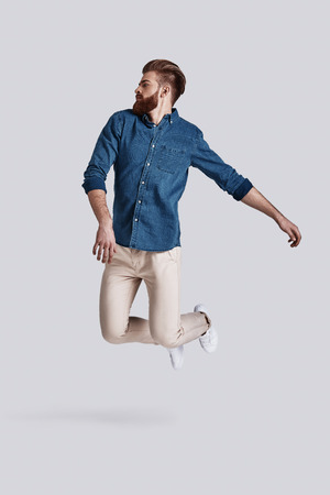 Feeling free to do anything.  Full length of handsome young man keeping eyes closed while jumping against grey background