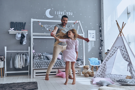 Just dance! Full length of father and daughter holding hands and smiling while dancing in bedroom