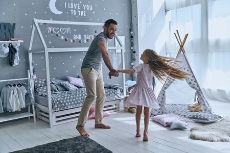Bailando con la princesa. Longitud total de padre e hija de la mano y sonriendo mientras que el baile en el dormitorio