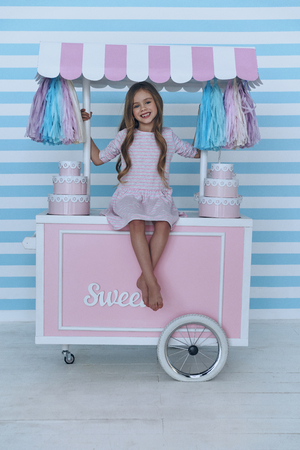 Princess on candy cart.  Cute little girl looking at camera and smiling while sitting on the candy cart decoration Stock Photo