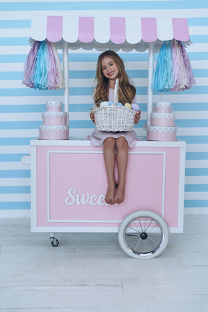 Lovely child.  Cute little girl holding Easter basket and smiling while sitting on the candy cart decoration