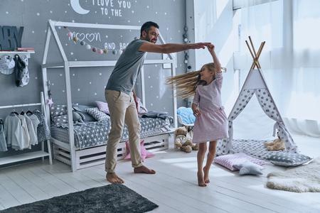 Spontane dans. Volledige lengte van vader en dochter hand in hand en lacht tijdens het dansen in de slaapkamer Stockfoto - 75978695