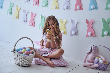 Feeling playful.  Cute little girl playing with duckling and smiling while sitting on the pillow with decoration in the background Stock Photo