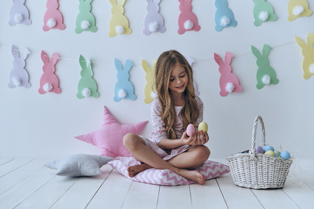 Delicious Easter treats. Cute little girl holding Easter eggs and smiling while sitting on the pillow with decoration in the background