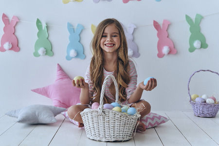 little one: Which one do you want?  Cute little girl holding Easter eggs and smiling while sitting on the pillow with decoration in the background Stock Photo