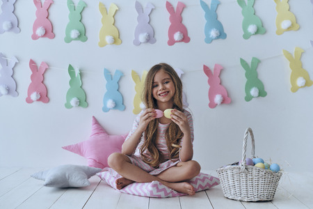 Excited about Easter. Cute little girl holding Easter eggs and smiling while sitting on the pillow with decoration in the background