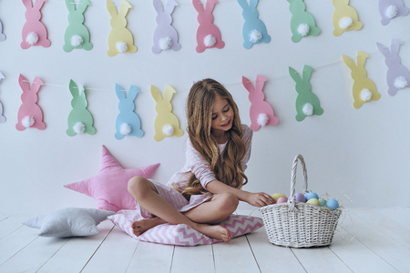 Collecting Easter eggs. Cute little girl putting an Easter egg in the basket and smiling while sitting on the pillow with decoration in the background