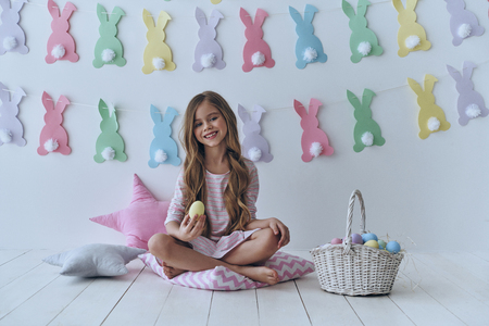 Easter fun. Cute little girl holding an Easter egg and smiling while sitting on the pillow with decoration in the background