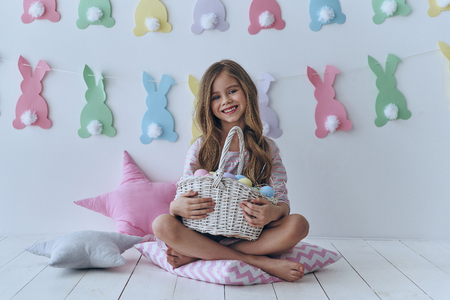 Ready to celebrate.  Cute little girl holding Easter basket and smiling while sitting on the pillow with decoration in the background
