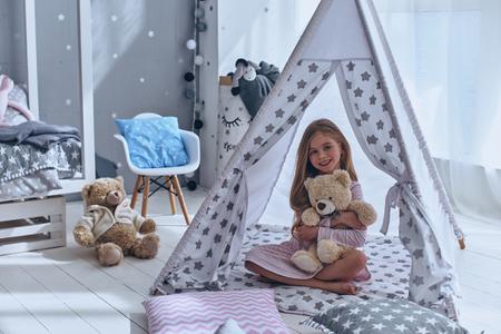 面白い友達!素敵な女の子彼女のおもちゃのクマを受け入れ、テントの床に座ってカメラ目線 写真素材