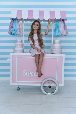 Lovely child.  Cute little girl looking at camera and smiling while sitting on the candy cart decoration