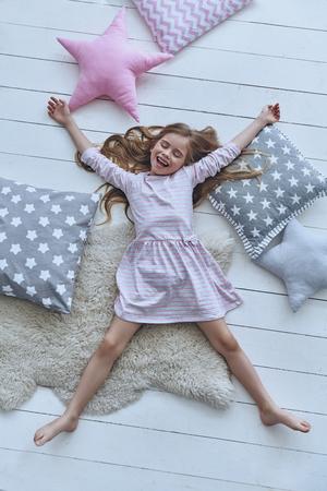 Verspieltes Mädchen. Draufsicht auf niedliche kleine Mädchen halten die Augen geschlossen und lächelt, während unter Kissen auf dem Boden liegend