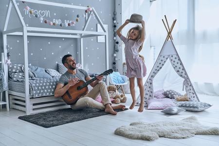 Trots op zijn dochter. Jonge vader die zijn kleine dochter bekijken en glimlachen terwijl zij die in slaapkamer springen