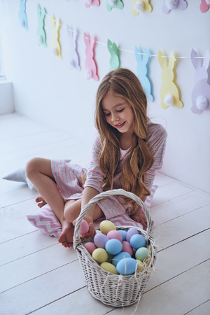 Getting ready to Easter. Lovely little girl holding an Easter egg and smiling while sitting on the pillow with decoration in the background
