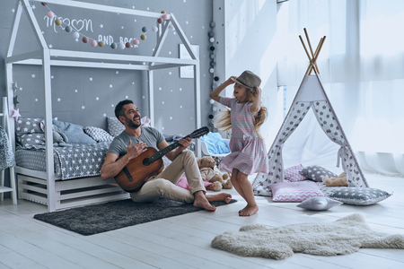 Having fun together. Young father playing guitar for his little daughter and smiling while spending free time at home 스톡 콘텐츠